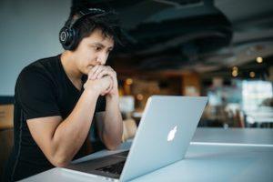 мужчина в наушниках сидит напротив компьютера