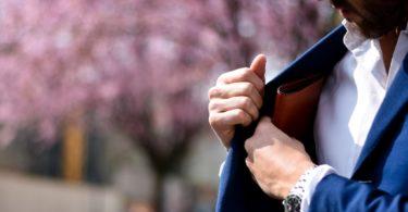 мужчина в синем костюме кладет кошелек во внутренний карман