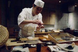 повар ресторана азиатской кухни готовит блюдо