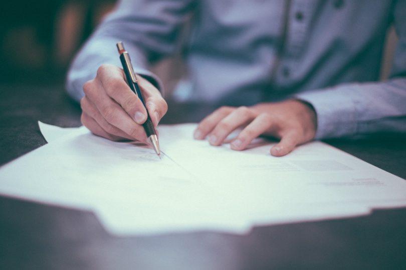 человек в голубой рубашке подписывает документы