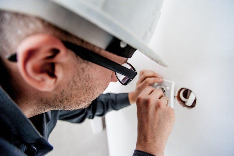 электрик чинит розетку в белой каске