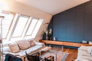 диван в комнате с большими окнами и зеленой стеной