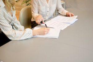 две девушки с бумагами сидят за столом