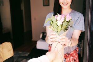 девушка принимает букет цветов