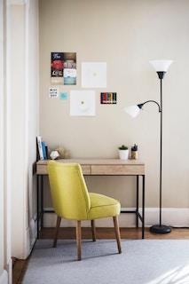 деревянный стол с желтым креслом и торшером