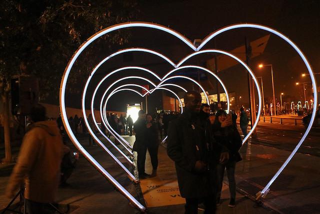 люди в инсталляции из света в форме сердца