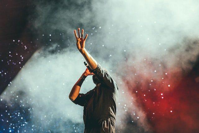мужчина с микрофоном поднимает левую руку на сцене