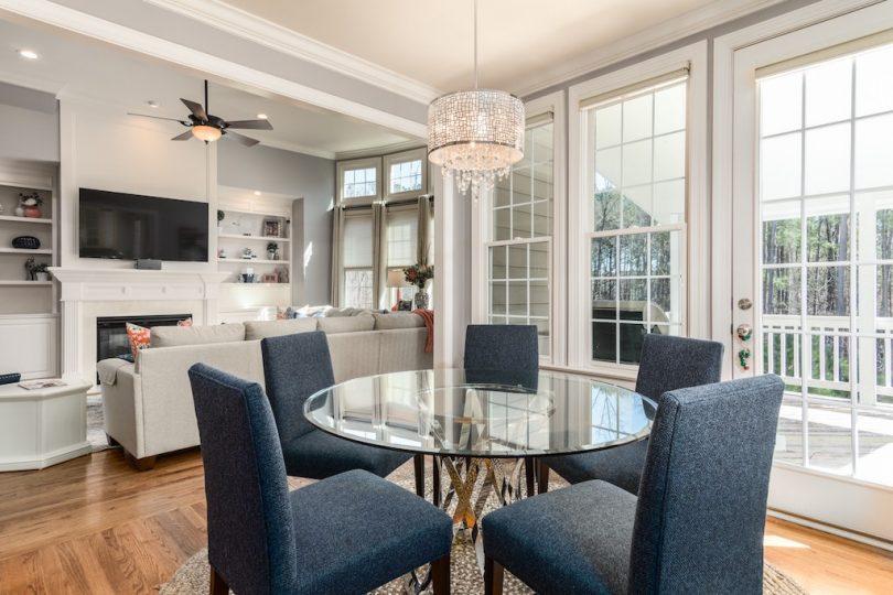 интерьер кухни в круглым столом, серыми стульями и большими окнами
