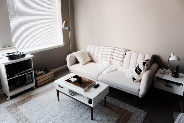 комната с белым дивана, столиком и закрытыми жилюзями