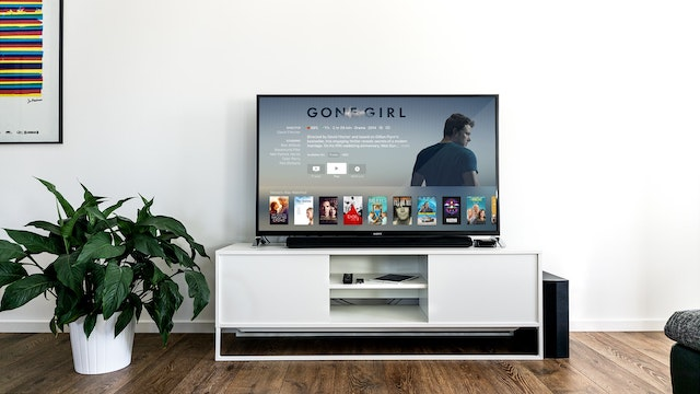 телевизор на белой тумбочке и растение