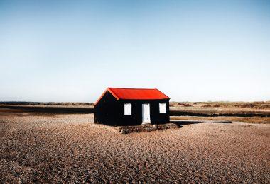 черный дом с красной крышей в пустыне