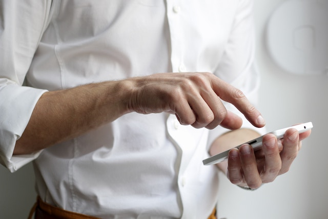 мужчина в белой рубашке с телефоном