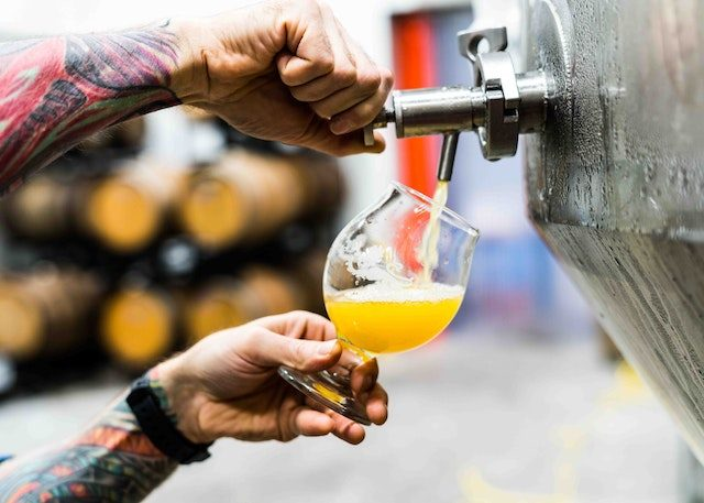 мужчина наливает бокал пива