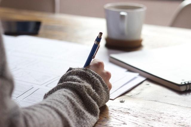 девушка пишет ручкой на бумаге