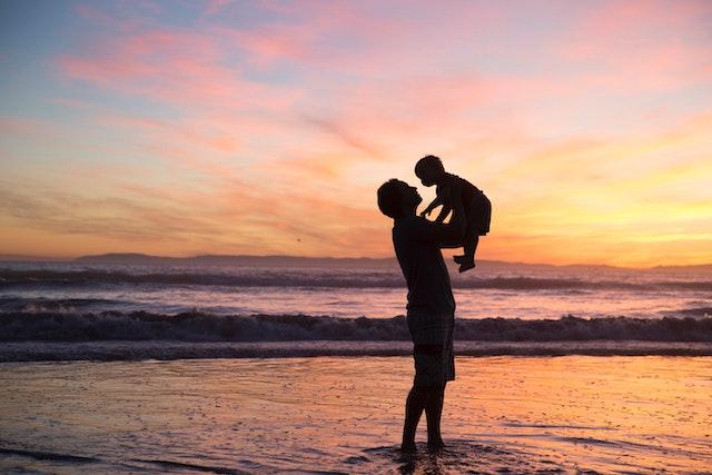 мужчина держит своего ребенка на фоне заката на море