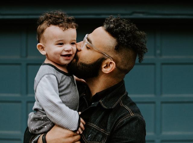 отец целует своего ребенка в щеку