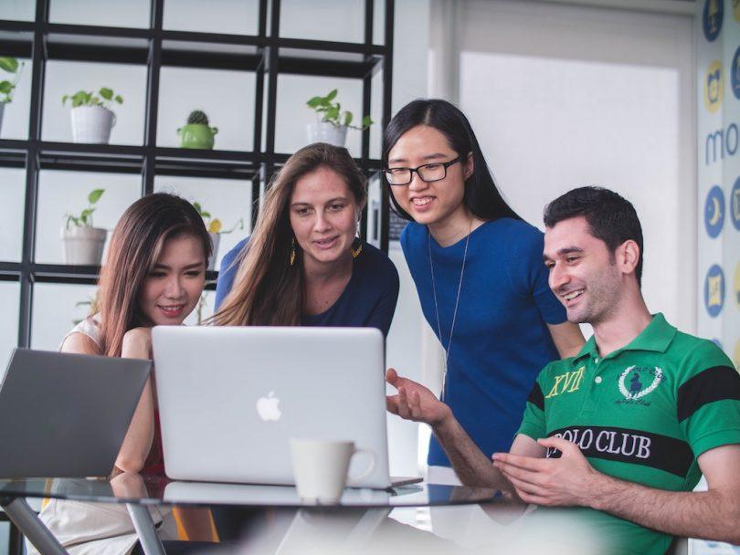 три девушки и один парень сидят перед компьютером