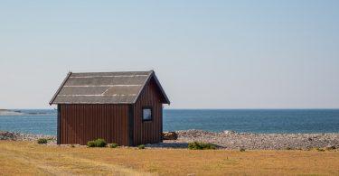 небольшой деревянный дом стоит у моря