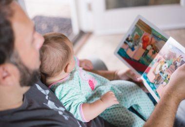 мужчина читает книгу ребенку на руках