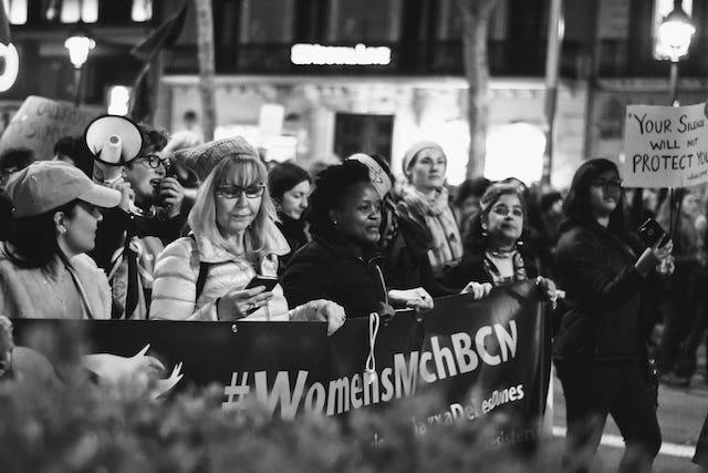 женщины стоят с плакатом