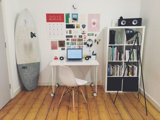 комната с белым столом, книжной полкой и зеркалом
