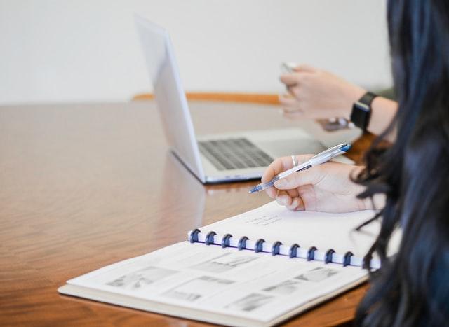 девушка держит в руках ручку с блокнотом