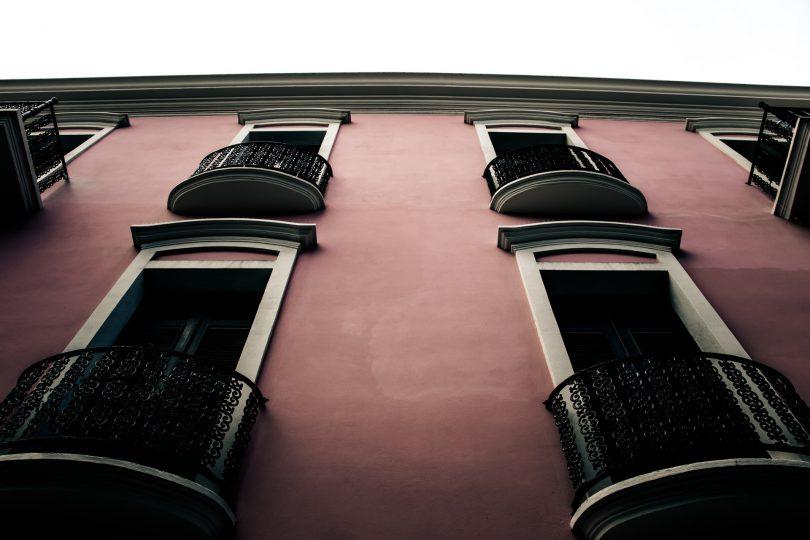 розовый фасад здания с балконами