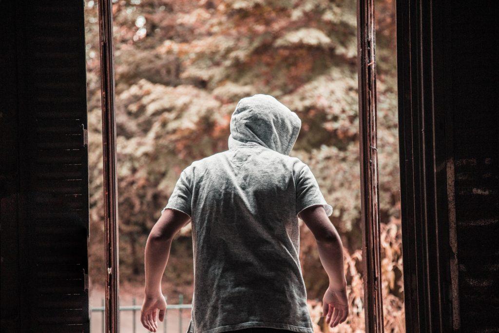 мужчина в капюшоне стоит спиной