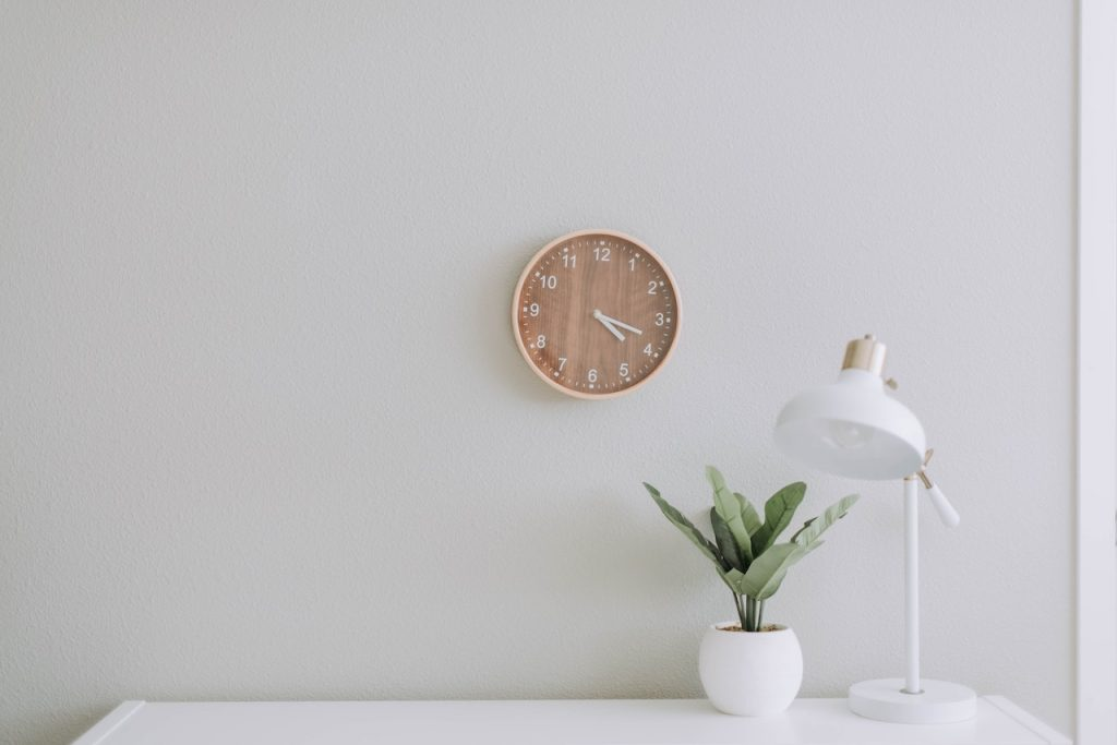 белые лампа, вазон и часы на белой стене