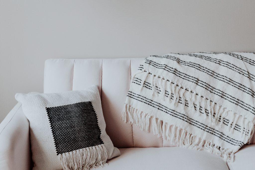 белые диван с подушкой и пледом