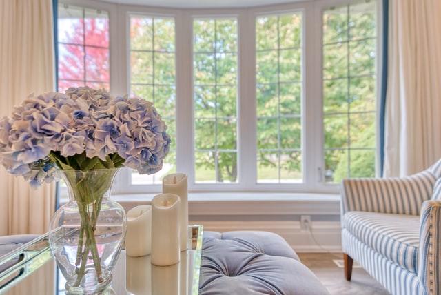 цветы, свечи и диван на фоне больших окон