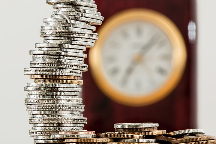 башня из монет на фоне часов