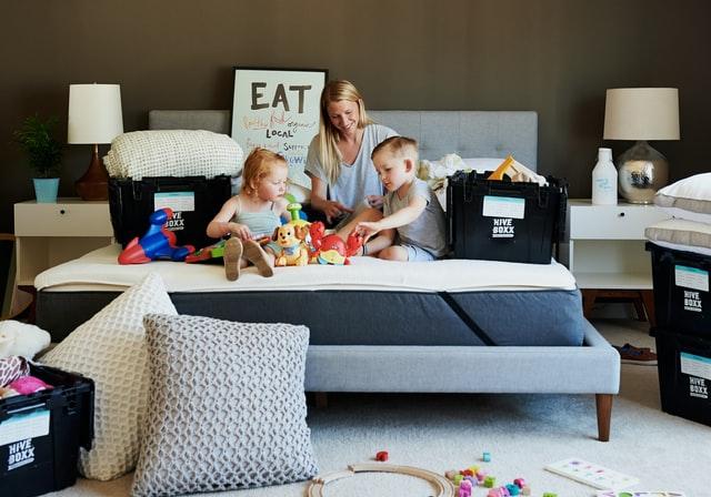 женщина и двое детей сидят на кровати