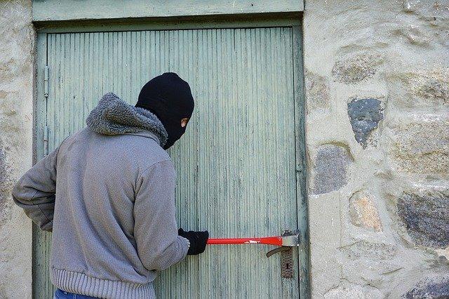 мужчина в маске взламывает дверь